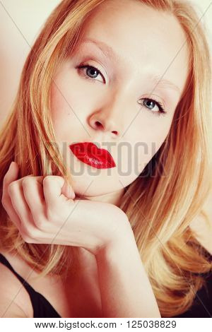 Vintage style portrait of young beautiful blond woman with red lipstick, selective focus