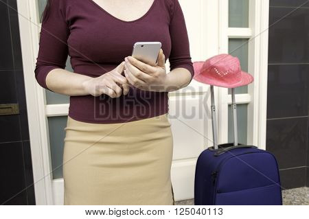 woman is calling to the taxi with the smartphone and waiting at the doorway of home with the suitcase and pink hat to go in vacations