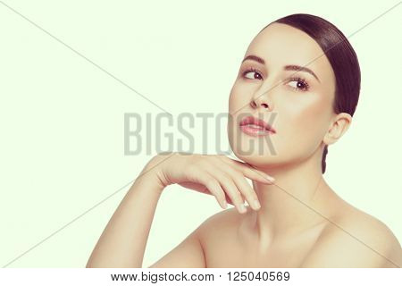 Vintage style portrait of young beautiful healthy happy woman touching her face and looking upwards