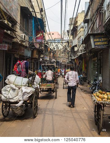 DELHI INDIA - 19TH MARCH 2016: A view along streets of central Delhi showing cargo carts people and the outside of buildings.