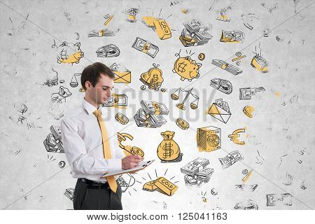 Businessman writing in notepad standing at concrete wall with money sketches