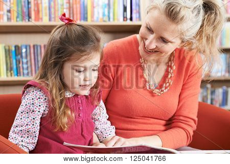 Mother And Daughter Reading Book In Library