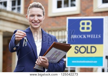 Portrait Of Female Realtor Holding Keys To New Home