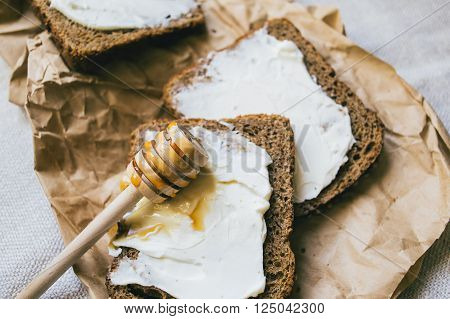 Sandwich with mascarpone cheese, honey and salad for healthy breakfast, close up