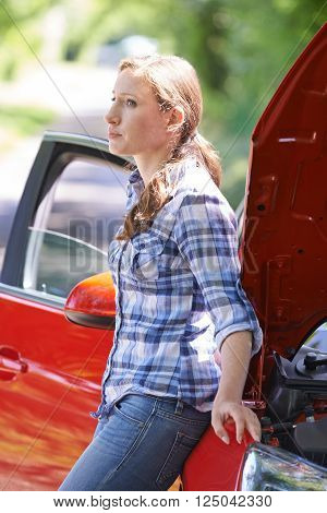 Worried Female Motorist Standing Next To Broken Down Car