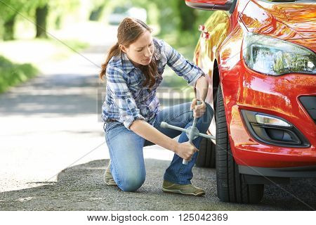 Frustrated Female Motorist Trying To Change Wheel On Country Road