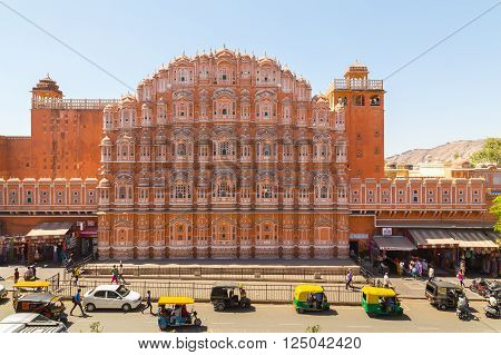 JAIPUR INDIA - 22ND MARCH 2016: A view of the Hawa Mahal (Palace of the Winds) in central Jaipur. Tuk Tuks other traffic and people can be seen outside on the street.