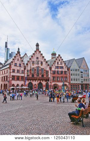 FRANKFURT GERMANY - APRIL 29 2012: Romer City Hall in Frankfurt in Germany. The Romerberg consists of old houses. Tourists nearby