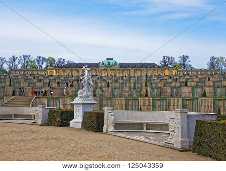 POTSDAM GERMANY - APRIL 30 2013: Summer palace and terrace in Sanssouci Park in Potsdam in Germany. It used to be a summer palace of King of Prussia Frederick the Great. Tourists nearby