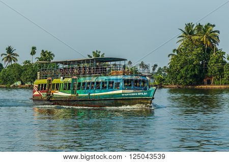 KERALA BACKWATERS INDIA - 1ST APRIL 2016: A colourful passenger boat in the Kerala backwaters of south India during the day. People can be seen.