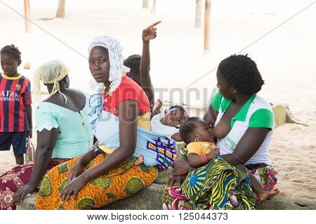 Abidjan, Ivory Coast - August 29,2015: young african women sitting on a coconut tree trunk in the shade.One breastfeeding her baby , another with a child on her back and a childless are in full chat.