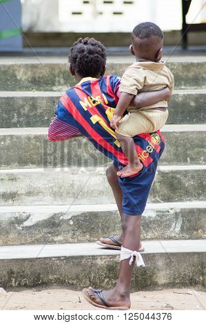 Abidjan , Ivory Coast - August 29, 2015: A small girl carrying a baby , left foot attached by a piece of cloth, goes up the stairs.