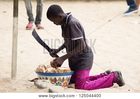 Abidjan, ivory coast - August 29, 2015: young boy , machete in  hand size a drowning coconut to sell it to a customer.