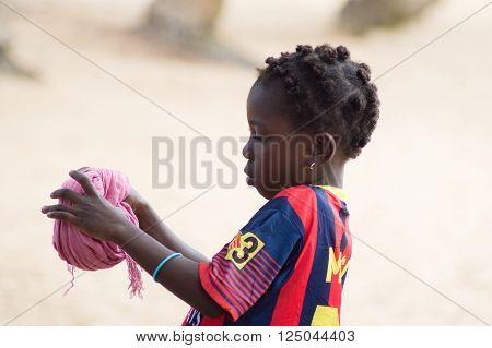 Abidjan, ivory coast - August 29, 2015: Alittle girl makes a cushion with a piece of fabric that will serve her to carry her goods.