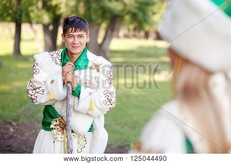 A man in a traditional festive dress of steppe nomads, leaned on his cane, looking at his wife.