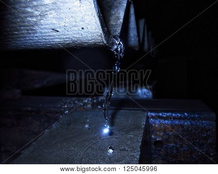 Water is flooding from roof and frozen due to flash light fired. One water drop is shining like diamond due to reflection of flash light.