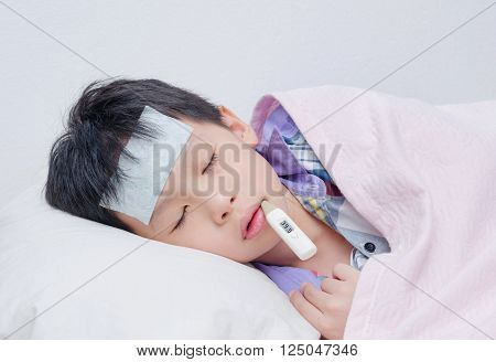 Little sick boy lying on bed with thermometer in mouth