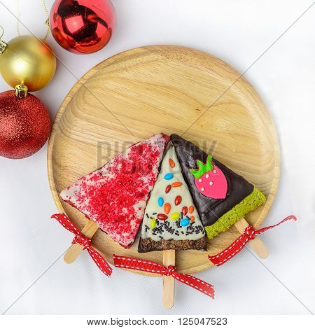 Home made brownies winter tree shape with red bow and ribbon on wooden plate; christmas glitter ball on white background