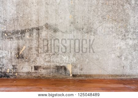 Home interior room repair concept - old gray concrete wall and dirty brown floor in repairing room