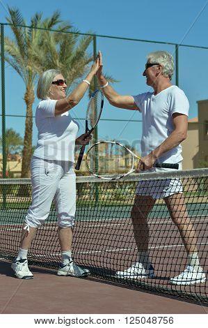 Portrait of a active senior couple on tennis court