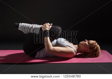 Young woman practicing yoga, Pawanmuktasana / Wind Relieving pose
