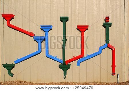 Colorful drain pipes on side of a building