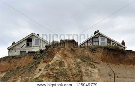 Homes in danger on the cliff edge at Happisburgh in Norfolk demonstrating levels of erosion along the East Coast. UK.