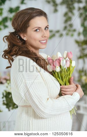 fashion photo of beautiful pregnant woman with long dark hair posing in studio interior with tulips.