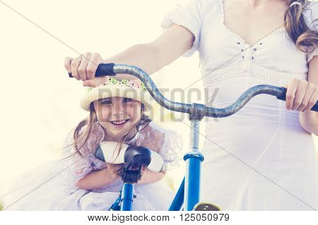 Beautiful mother and daughter traveling on a bicycle on a warm summer day.