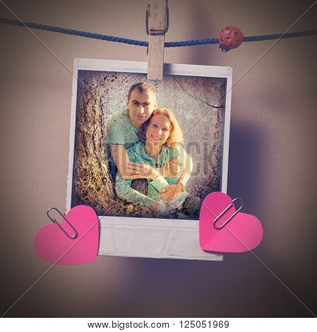 Couple in love instant photo and small red paper heart hanging on the clothesline. Photos in grunge style.