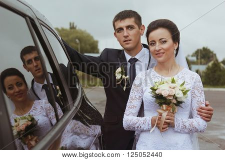 Bride with groom reflexion in a windowpane of car