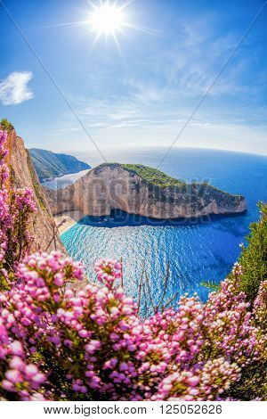 Navagio Beach With Shipwreck And Flowers Against Sunset On Zakynthos Island In Greece