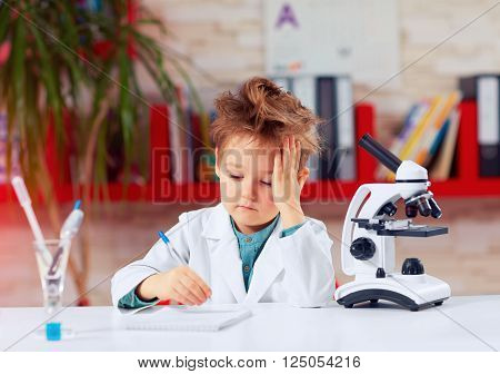 Tired Little Scientist Writing Notes After Experiments In School Lab