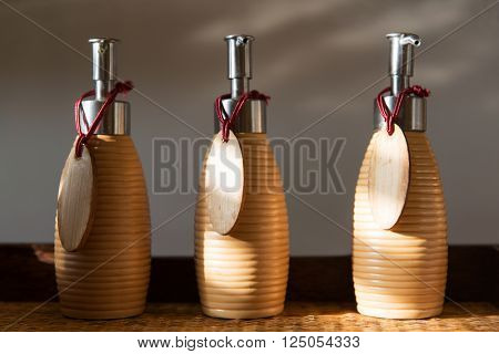 beauty, body care, luxury, natural cosmetics and hygiene concept - close up of liquid soap or body lotion set with blank  wooden nameplates at hotel bathroom