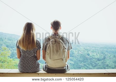 Back view of a young man and woman enjoying amazing view while sitting on a high mountain in sunny day two travelers resting.