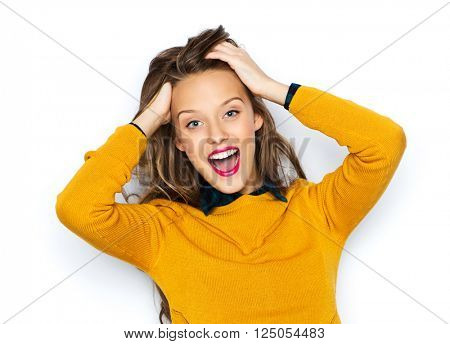 people, style, hairstyle and fashion concept - happy young woman or teen girl in casual clothes holding touching hair