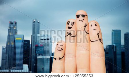 travel, tourism, family, people and body parts concept - close up of four fingers with smiley faces over singapore city skyscrapers background