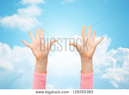 people, childhood, gesture and body parts concept - close up of little child hands raised up over blue sky and clouds background