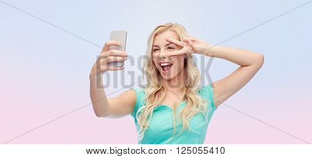 emotions, expressions and people concept - happy smiling young woman or teenage girl taking selfie with smartphone over rose quartz and serenity gradient background
