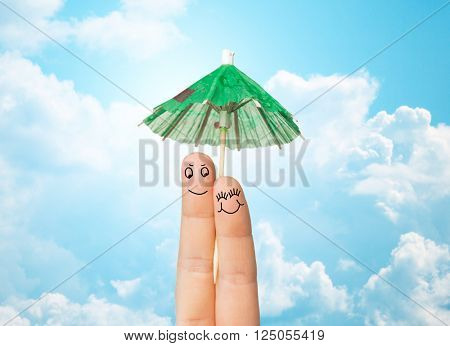 gesture, love, holidays, summer vacation and body parts concept - close up of two fingers with cocktail umbrella decoration over blue sky and clouds background