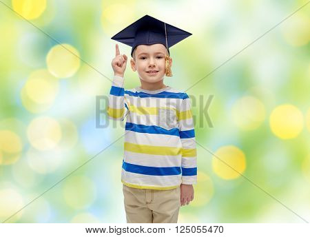 childhood, school, education, learning and people concept - happy boy in bachelor hat or mortarboard pointing finger up over summer green lights background