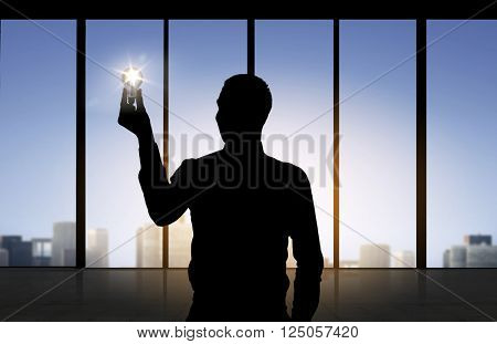 business, inspiration, idea and people concept - silhouette of businessman holding alight light bulb over office window background