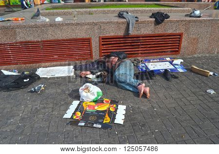 Dirty poor homeless man sleeps on Khreshatik - central street of Kiev.At April 8,2016 in Kiev, Ukraine