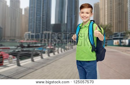 childhood, school, education and people concept - happy smiling student boy with school bag over dubai city street background