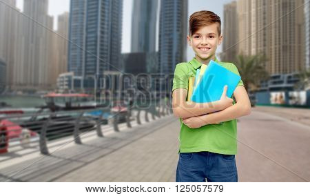 childhood, school, education and people concept - happy smiling student boy with folders and notebooks over dubai city street background