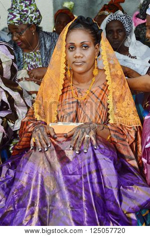 Abidjan, Ivory coast -February 26;2015: Ayoung newly married woman is being celebrated. Beautiful , this young woman sitting tattoo hands, well makeup, site and admires her wedding party.