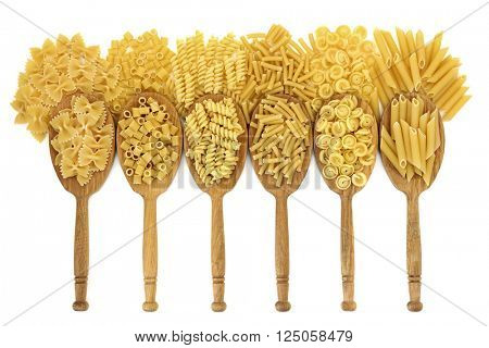 Dried pasta food varieties in oak wood spoons and loose over white background. Farfalle, ditali rigati, fusilli, macaroni, messicani and penne varieties from left to right.