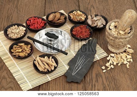 Acupuncture needles, moxa sticks, traditional chinese herbs for herbal medicine and mortar with pestle over bamboo and old oak background.
