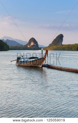 Sunset view of Krabi River with long-tail boat and limestone karst cliffs Krabi Town Thailand