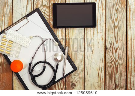 Medical supplies and stethoscope on wooden background